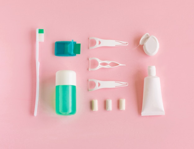 Tandenborstels, tandpasta, spoeling en kauwgom op roze