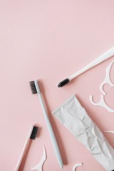 Tandenborstels, tandpasta, tandflossers op roze