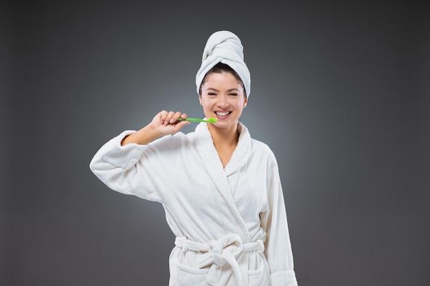 Tandenpoetsen en mondverzorging. een lachend meisje in een badjas en met een handdoek om haar hoofd gewikkeld na het baden, met een tandenborstel in haar hand om haar tanden te poetsen