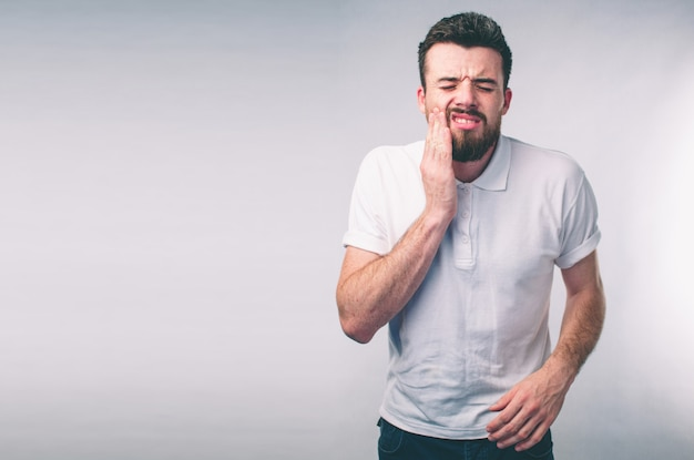 Tandenprobleem. man gevoel tand pijn. close-up van gebaarde jongen die aan sterke tandpijn lijden. aantrekkelijke mannelijke gevoel pijnlijke kiespijn. tandheelkundige gezondheid en zorg concept