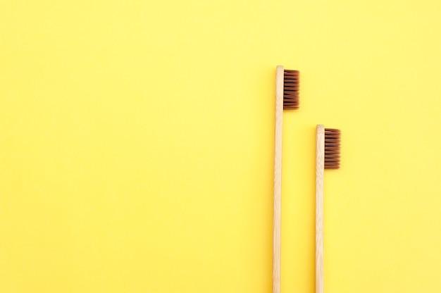 Tandheelkunde. bamboe tandenborstel op een gele achtergrond. ecologie. ruimte voor tekst
