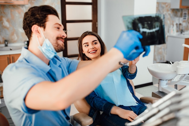 Tandheelkunde en gezondheidszorgconcept, mannelijke tandarts die tandenröntgenstraal toont aan vrouwelijke patiënt bij tandkliniekruimte.