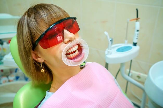 Tandheelkunde gelukkige patiënt als voorzitter in beschermende brillen.