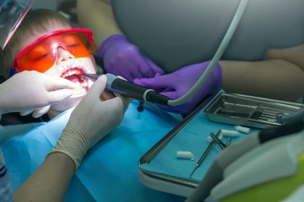 Tandheelkunde voor kinderen. kindertandarts onderzoek melktanden. kleine jongen in beschermende oranje glazen en kofferdam. behandeling van cariës. selectieve aandacht, kunstmatige ruis