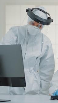 Tandheelkundeteam van specialisten met pbm-pakken die computer gebruiken voor moderne tandheelkundige zorg. verpleegkundige zit aan bureau, kijkt naar monitor terwijl tandarts het scherm analyseert tijdens covid pandemie