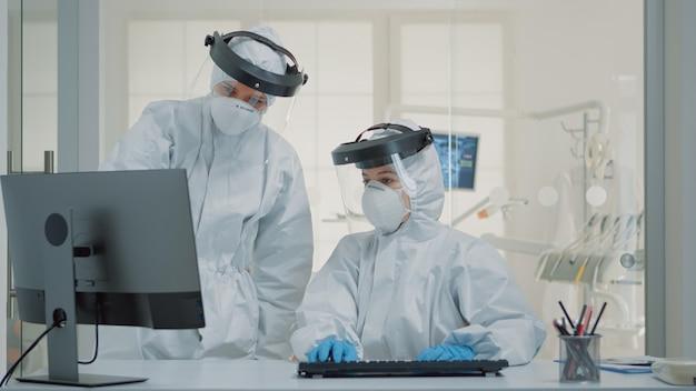 Tandheelkundig team van specialisten met pbm-pakken met behulp van computer