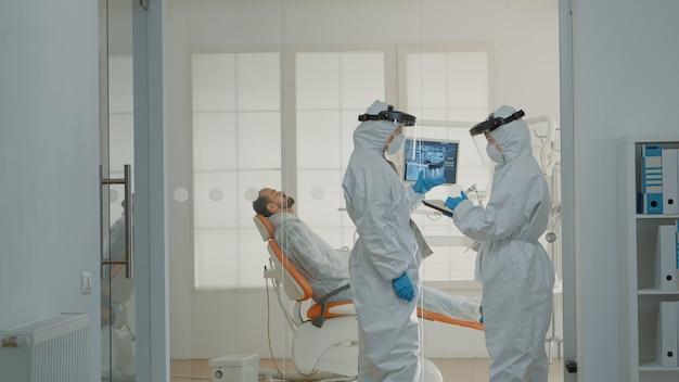 Tandheelkundig team van tandartsen die patiënt in kabinet raadplegen