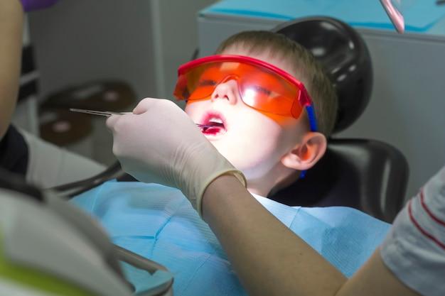 Tandheelkundige geneeskunde voor kinderen. mondeling of tandheelkundig onderzoek door tandarts met medische apparatuur. kindertandarts onderzoek melktanden. emoties van een kind in een tandartsstoel.