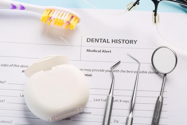 Tandheelkundige geschiedenis met professionele stalen tandheelkundige instrumenten, spiegel en tandzijde in de buurt van tandenborstel en bril