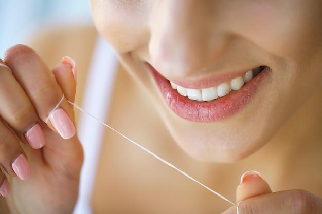 Tandheelkundige gezondheid. vrouw met mooie glimlach flossing gezonde tanden. beeld