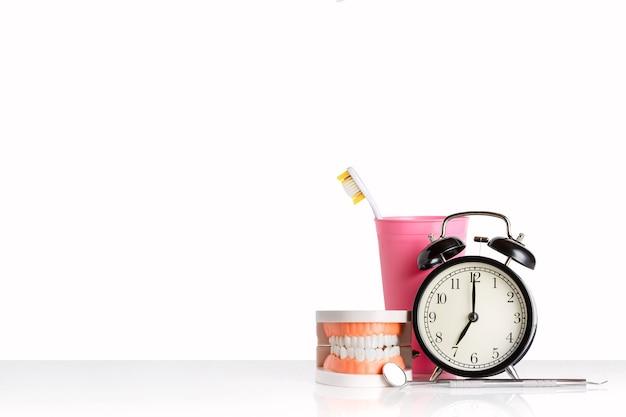 Tandheelkundige instrumenten dichtbij menselijke kaak, wekker en tandenborstel