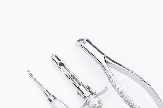 Tandheelkundige instrumenten en apparatuur op een witte achtergrond.