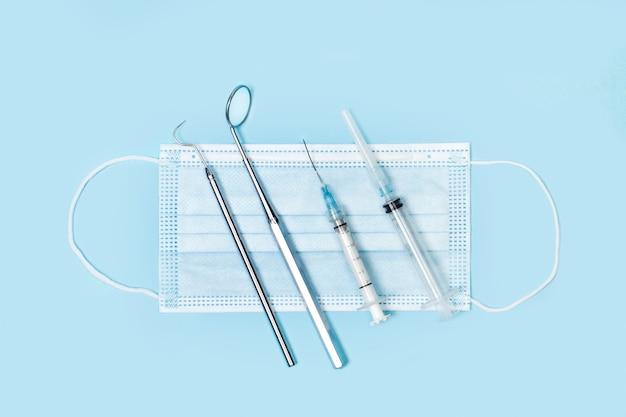 Tandheelkundige instrumenten en spuiten op een operatiemasker en op een lichtblauw oppervlak
