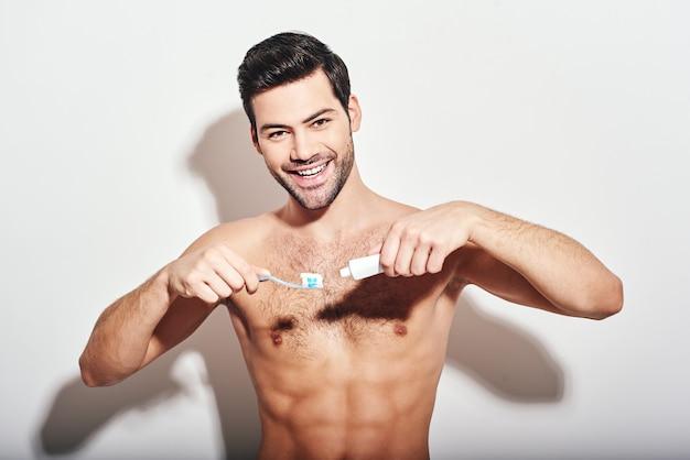 Tandheelkundige jonge donkerharige man die shirtloos staat en tandpasta op een tandenborstel knijpt
