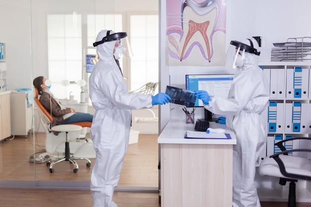 Tandheelkundige receptioniste gekleed in overall gezicht shiled geven arts patiënt röntgenfoto's houden sociale afstand tijdens covid19 virus pandemie