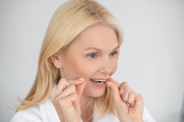 Tandheelkundige vlek. een portretfoto van een vrouw die haar tanden met een tandzijde poetsen