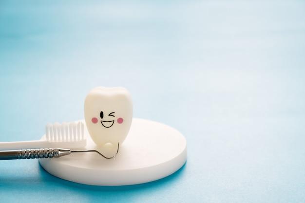 Tandhulpmiddelen en glimlachtandenmodel op blauwe achtergrond.