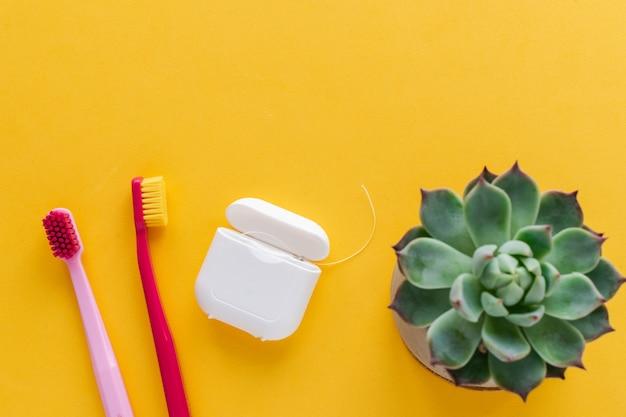 Tandhygiëne tandenborstels, tandzijde, mondwater plat, bovenaanzicht, copyspace, geel