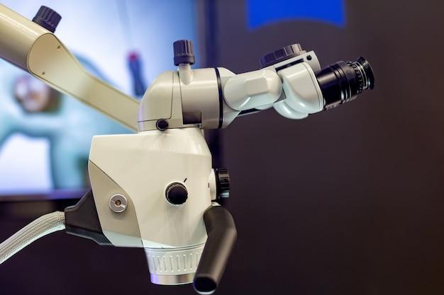 Tandmicroscoop op de achtergrond van moderne tandheelkunde. medische apparatuur. tandheelkundige operatiemicroscoop met roterende dubbele verrekijker.