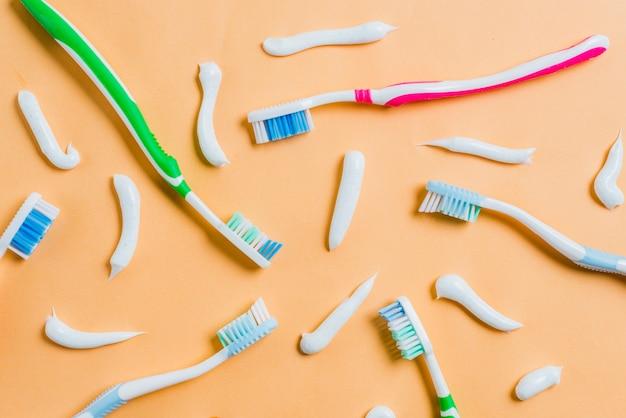 Tandpasta met verschillende soorten tandenborstels op gekleurde achtergrond