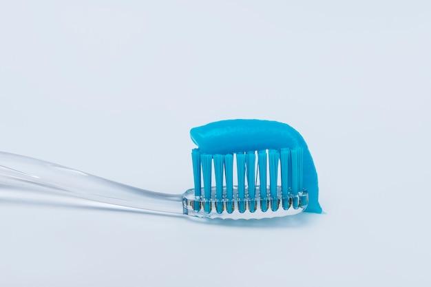 Tandpasta op een tandenborstel op een witte achtergrond.