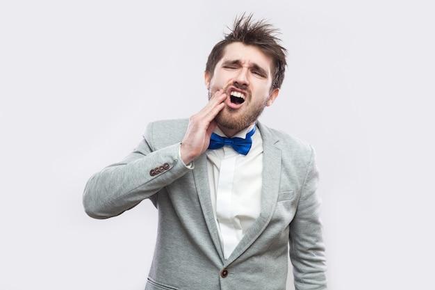 Tandpijn of pijn. portret van een zieke knappe bebaarde man in een casual grijs pak en een blauwe vlinderdas die staat en zijn wang aanraakt vanwege tandpijn. indoor studio-opname, geïsoleerd op lichtgrijze achtergrond