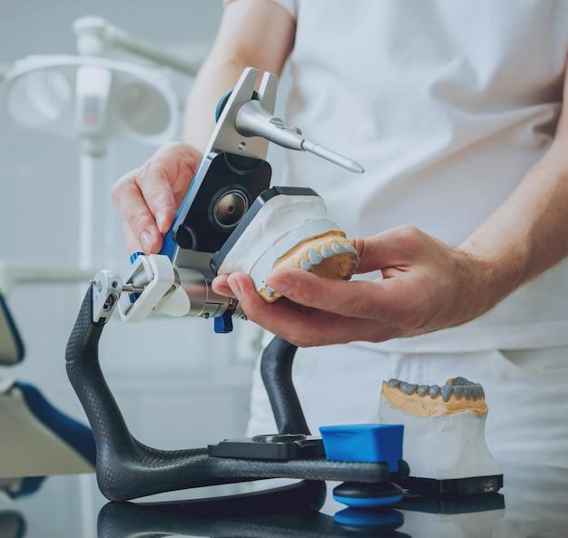 Tandtechnicus die met gewricht in tandlaboratorium werkt