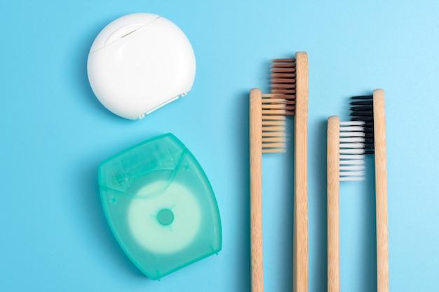 Tandzijdecontainers en bamboetandenborstels op blauwe achtergrond. dagelijkse mondhygiëne, tandverzorging en gezondheid. reinigingsproducten voor mond. tandheelkundige zorg concept.