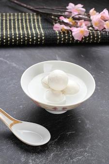 Tang yuan (wedang ronde), chinese kleefrijst knoedel ballen met suiker gember siroop op chinese kom op zwarte achtergrond voor winterzonnewende nieuwjaar festival voedsel.