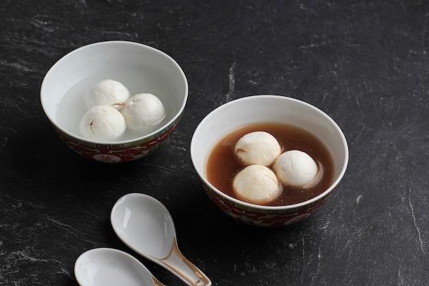 Tang yuan (wedang ronde), chinese kleefrijst knoedelballen met suikergember of palmsuikersiroop op rood chinees op zwarte achtergrond voor winterzonnewende nieuwjaarsfestivalvoedsel.