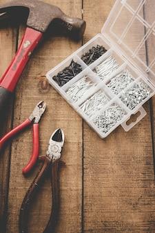 Tangen, hamer en nagel organisator op houten tafel. oude tools. kopieer ruimte.
