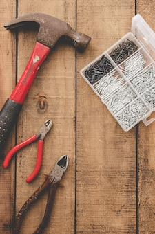 Tangen, hamer en nagel organisator op houten tafel. oude tools.