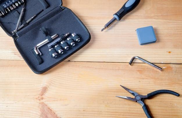 Tangen, schroevendraaiers, moersleutels, meters en andere een draagbare gereedschapskit voor technicus op houten plaat.