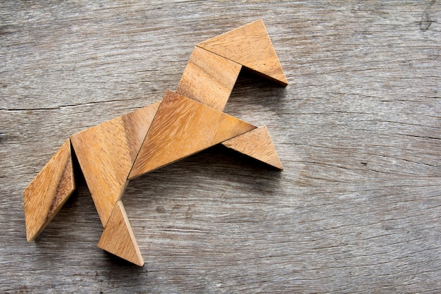 Tangrampuzzel in paard opwindende vorm op houten achtergrond