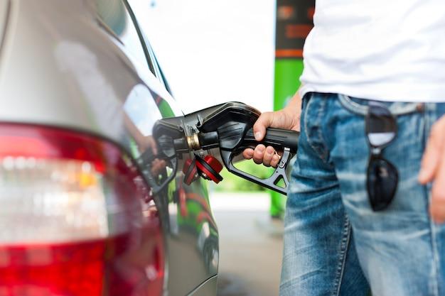 Tank de auto bij een benzinestation