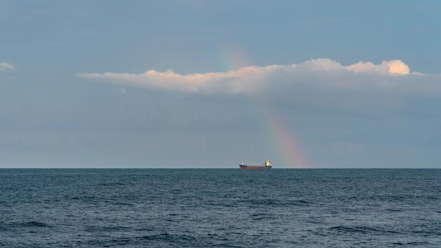 Tankers op zee horizon en korte brede regenbogen, wolken in de lucht. landschap