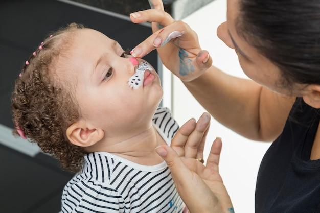 Tante schildert het gezicht van het kind met haar vingers.