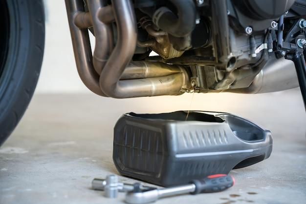 Tap de oude olie van de motor af via de aftapplug. verversen van de olie in een motorfietsmotor