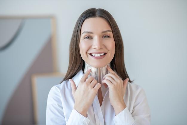 Taping. leuke jonge vrouw tapes op haar nekspier zetten en glimlachen
