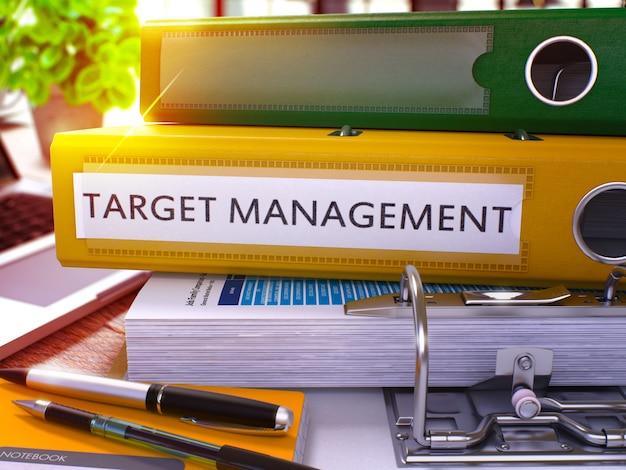 Target management - gele ringband op office desktop met kantoorbenodigdheden en moderne laptop. doel management business concept op onscherpe achtergrond. 3d-weergave.