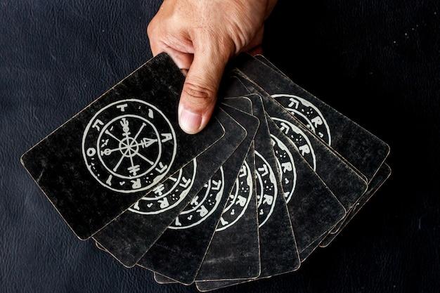 Tarotkaart voor het kiezen van astrologisch in zijn hand op zwarte achtergrond