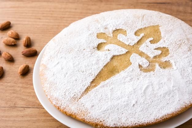 Tarta de santiago. traditionele amandelcake van santiago in spanje op houten lijst