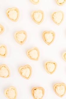 Tartlet van de hartvorm met verse die room wordt op witte achtergrond wordt geïsoleerd gevuld die