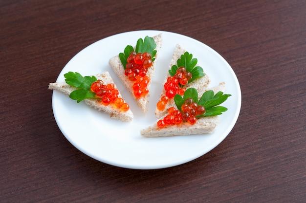Tartlets met kaviaar en peterselie op een bord