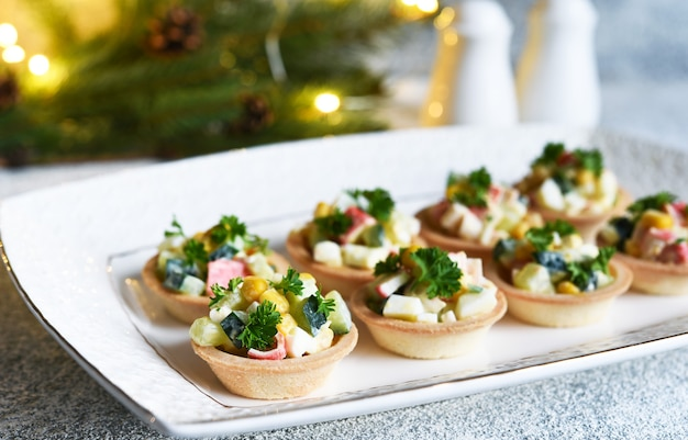 Tartlets met krabsticks en maïs en champagne in een glas op de nieuwjaarstafel.