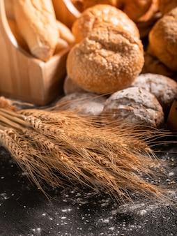 Tarwe en groep brood op de zwarte houten tafel