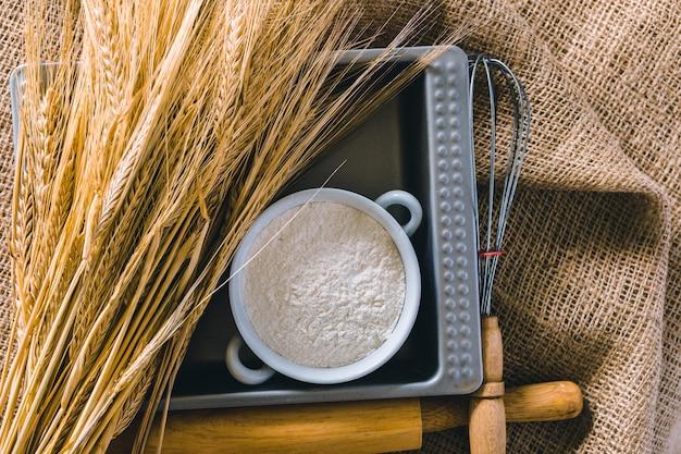 Tarwe en keukengereedschap op jute