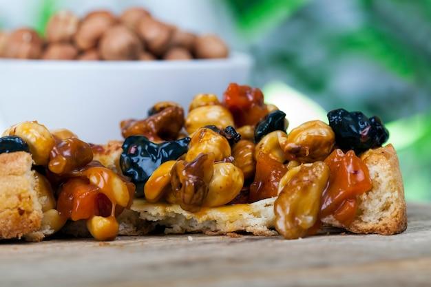 Tarwedeegtaartje met noten en gedroogde vruchten in roomkaramel, tarwetaartje met zoete vulling, krokant taartje met hazelnoten, pinda's en andere ingrediënten