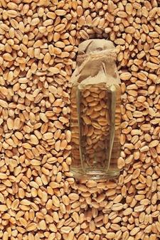 Tarwekiemolie. tarweolie in een transparante fles met een papieren deksel in tarwekorrels