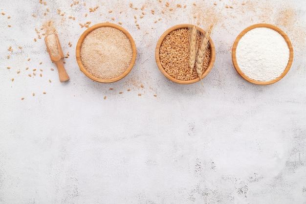 Tarwekorrels, bruin tarwemeel en wit tarwemeel in houten kom opgezet op witte betonnen ondergrond.